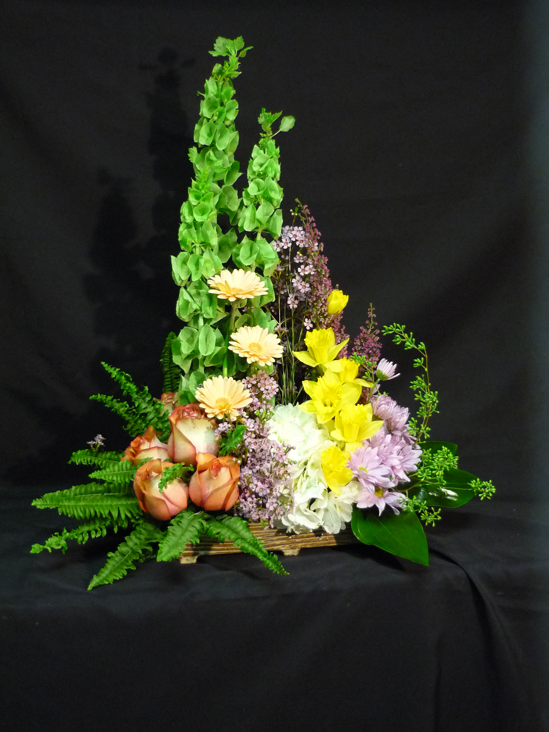 Gallery the flowers form a garden setting against a tall green back drop of bells of ireland gerberas daffodils hydrangeas roses and wax izmirmasajfo